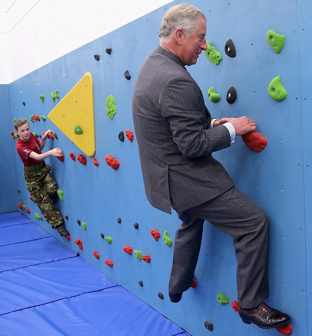 The Prince of Wales climbs on the new traversing wall at Grainville Secondary School
